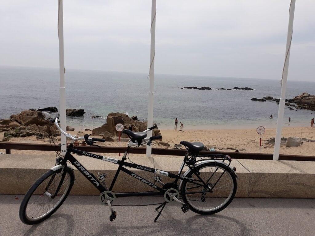Bicicleta de dois lugares a passear à beira mar
